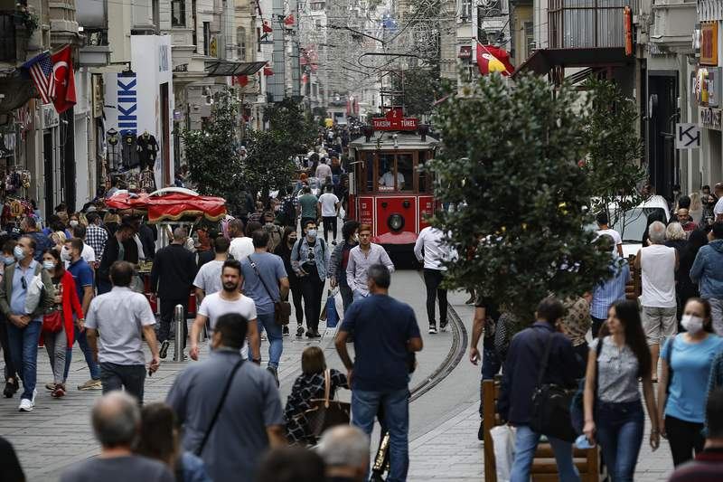 People, most wearing masks to help protect against the spread of coronavirus, walk along Istiklal street, the main shopping street in Istanbul, Friday, Oct. 9, 2020. (AP Photo/Emrah Gurel)