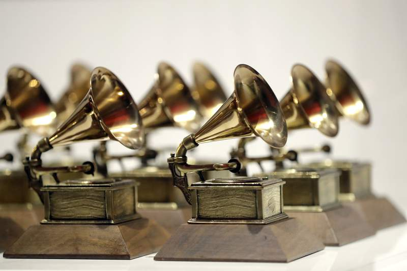 """FILE - In this Oct. 10, 2017, file photo, various Grammy Awards are displayed at the Grammy Museum Experience at Prudential Center in Newark, N.J. The Recording Academy is partnering with Berklee College of Music and Arizona State University to complete a study focused on women's representation in the music industry.. The academy, which puts on the annual Grammy Awards, said the lack of female creators in music is one of the most urgent issues in the industry today."""" (AP Photo/Julio Cortez, File)"""