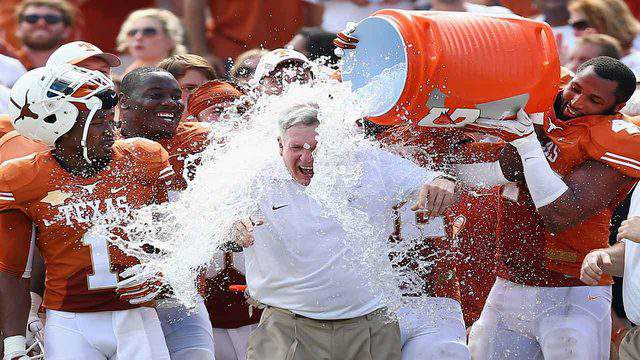 Texas Longhorns head coach Mack Brown, who came out of retirement to return to his previous job at North Carolina, has ice water dumped on him by his team, Oct. 12, 2013, in Dallas.