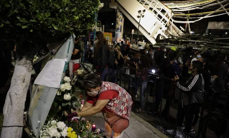 Una mujer coloca flores en un altar improvisado durante una protesta el viernes 7 de mayo de 2021 en demanda de justicia para las personas que fallecieron el lunes debido a un derrumbe en un tramo elevado del metro en la Ciudad de Mxico. (AP Foto/Eduardo Verdugo)