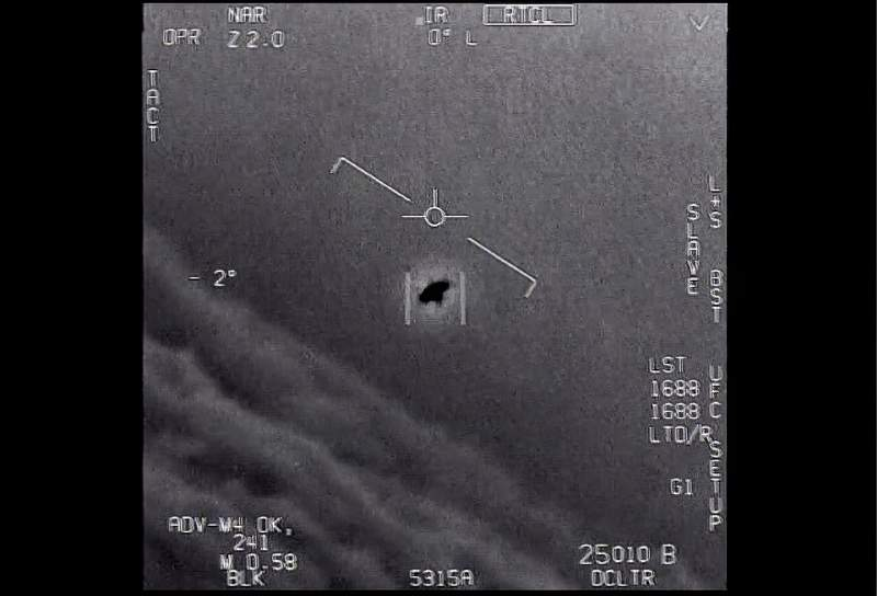 """The image from video provided by the Department of Defense labelled Gimbal, from 2015, an unexplained object is seen at center as it is tracked as it soars high along the clouds, traveling against the wind. There's a whole fleet of them, one naval aviator tells another, though only one indistinct object is shown. It's rotating."""" The U.S. government has been taking a hard look at unidentified flying objects, under orders from Congress, and a report summarizing what officials know is expected to come out in June 2021. (Department of Defense via AP)"""