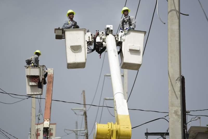 ARCHIVO - En esta foto del 19 de octubre del 2017, trabajadores de la Autoridad de Energa Elctrica de Puerto Rico trabajan en cables daados por el huracn Mara en la comunidad Cantera en San Juan.  (AP Foto/Carlos Giusti)