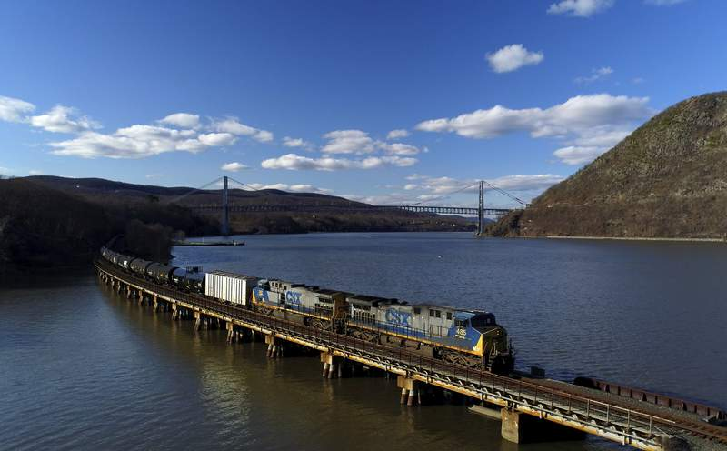 FILE- In this April 26, 2018, file photo, a CSX Transportation locomotive pulls a train of tank cars across a bridge on the Hudson River along the edge of Bear Mountain State Park near Fort Montgomery, N.Y. CSX railroads second-quarter profit more than doubled as the economy continued to rebound from the depths of the coronavirus pandemic, the company announced Wednesday, July 21, 2021. (AP Photo/Julie Jacobson, File)
