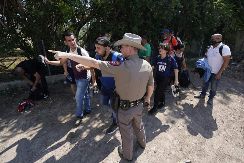 FILE - In this Wednesday, June 16, 2021 file photo, A Texas Department of Public Safety officer in Del Rio, Texas directs a group of migrants who crossed the border and turned themselves in. he Biden administration sued Texas on Friday, July 30, 2021 to prevent state troopers from stopping vehicles carrying migrants on grounds that they may spread COVID-19, warning that the practice would exacerbate problems amid high levels of crossings on the state's border with Mexico. (AP Photo/Eric Gay, File)