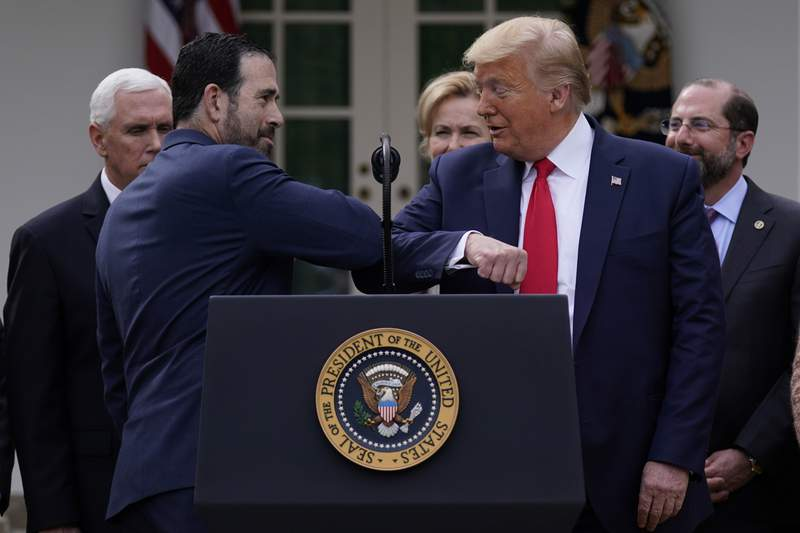 LHC Groups Bruce Greenstein elbow bumps with President Donald Trump during a news conference about the coronavirus in the Rose Garden at the White House, Friday, March 13, 2020, in Washington. (AP Photo/Evan Vucci)
