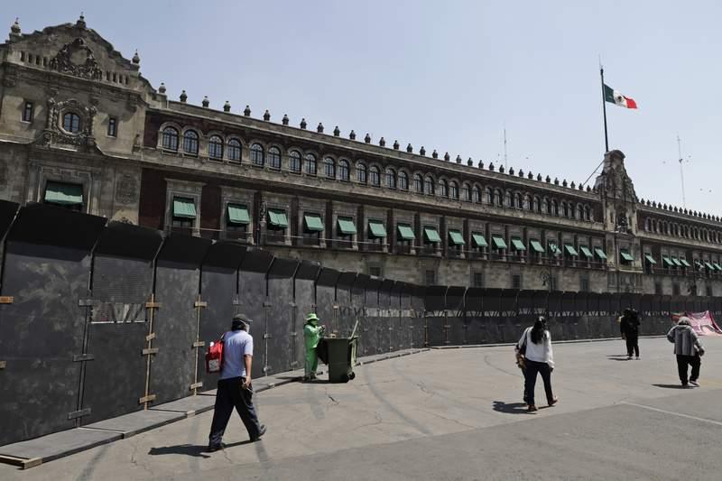 Diversos transentes pasan el viernes 5 de marzo por un permetro de barreras colocadas alrededor del Palacio Nacional, en la Ciudad de Mxico, en antelacin a las protestas feministas con motivo del Da Internacional de la Mujer. (AP Foto/Eduardo Verdugo)
