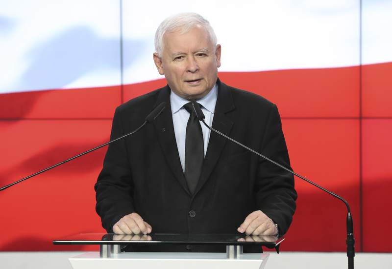 The leader of the Polish ruling party, Jaroslaw Kaczynski,center, speaks to reporters in Warsaw, Poland, Saturday, Sept. 26, 2020. The three parties in Poland's conservative coalition government signed a new coalition agreement on Saturday, putting aside disagreements. But they gave no details, leaving lingering uncertainty about how the Cabinet will look in practice after an expected reshuffle.(AP Photo/Czarek Sokolowski)