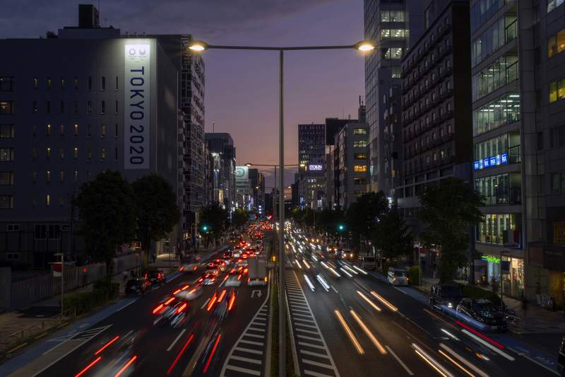 This long exposure photo shows streaks of lights from the cars passing by a Tokyo 2020 Olympics and Paralympics sign on the side of a building Monday, Oct. 12, 2020, in Tokyo, as the sky is colored by the sunset. (AP Photo/Kiichiro Sato)