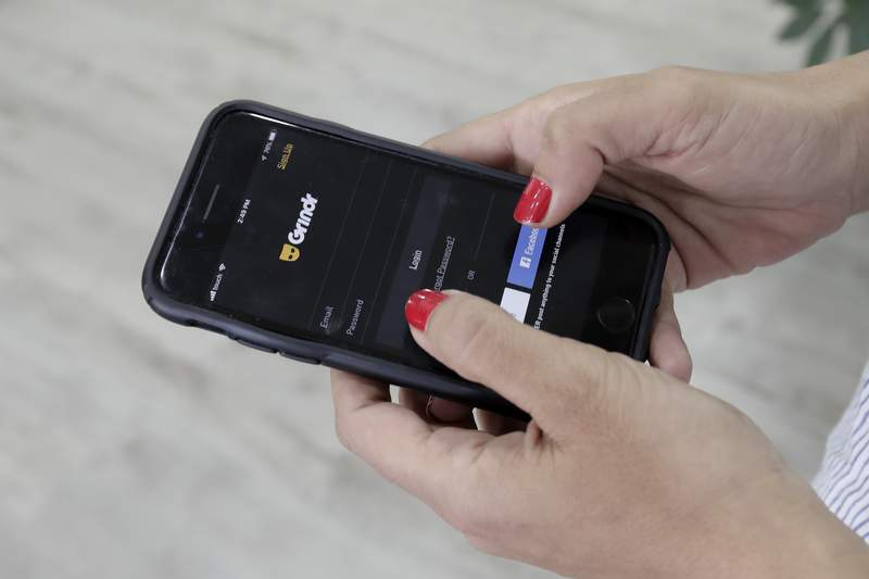 FILE - In this Wednesday, May 29, 2019 file photo, a woman looks at the Grindr app on her mobile phone in Beirut, Lebanon. With few rules in the U.S. guiding what companies can do with the vast amount of information they collect about what web pages people visit, the apps they use and where they carry their devices, theres little stopping similar spying activity targeting politicians, celebrities and just about anyone thats a target of another persons curiosity. (AP Photo/Hassan Ammar, File)
