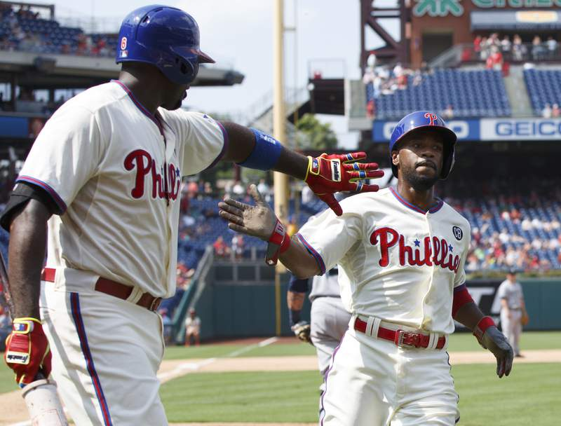 """FILE - In this Aug. 20, 2014, file photo, Philadelphia Phillies' Jimmy Rollins, right, celebrates his run with Ryan Howard on a single by Chase Utley during the fifth inning of the team's baseball game against the Seattle Mariners in Philadelphia. When Rollins made his first All-Star team as a rookie with the Phillies 20 years ago, the percentage of Black players in the majors was 13. Its down to 7.6% this year. Rollins pointed to Ken Griffey Jr. and Barry Bonds as popular players who were marketed well when he was growing up. But when you start going outside of that select few, the sport itself isnt marketing anyone else in a major way where kids from the inner cities are attracted to it,"""" he said. (AP Photo/Chris Szagola, File)"""