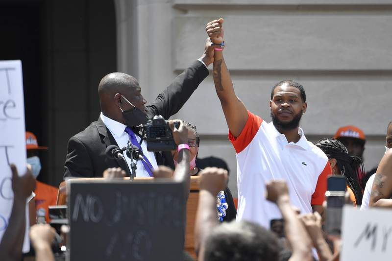 Attorney Benjamin Crump, left, holds up the hand of Kenneth Walker during a rally on the steps of the Kentucky State Capitol in Frankfort, Ky., Thursday, June 25, 2020. Walker was the boyfriend of Breonna Taylor who was killed by officers of the Louisville Metro Police Department following the execution of a no knock warrant on her apartment on March 13, 2020. (AP Photo/Timothy D. Easley)