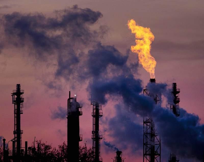 ARCHIVO - En esta foto del 4 de diciembre del 2018, llamas salen de una chimenea en la planta qumica de BASF en Ludwigshafen, Alemania. Compromisos recientes de Estados Unidos y otros pases pudieran ayudar a contener el calentamiento global a 2 grados Celsius (3,6 Fahrenheit) para el final del siglo, pero solamente si esfuerzos para reducir las emisiones de gases de invernadero a cero neto para el 2050 son exitosos, dicen cientficos. (AP Foto/Michael Probst)