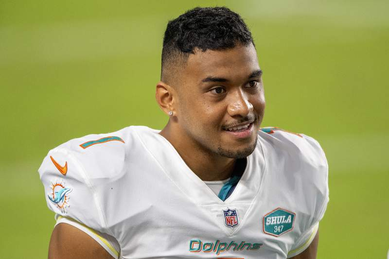 Miami Dolphins quarterback Tua Tagovailoa (1) smiles on the sidelines before playing for the first time against the New York Jets during an NFL football game, in Miami Gardens, Fla. Miami Dolphins coach Brian Flores says he regrets that his players found out about the team's switch to quarterback Tua Tagovailoa through social media rather than from him. And Flores says the decision to bench popular veteran Ryan Fitzpatrick was difficult.(AP Photo/Doug Murray)