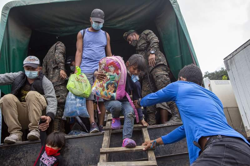 Una nia migrante hondurea es ayudada a salir de un camin tras haber sido retornada a El Florido, Guatemala, el 19 de enero del 2021. (AP Photo/Oliver de Ros, File).
