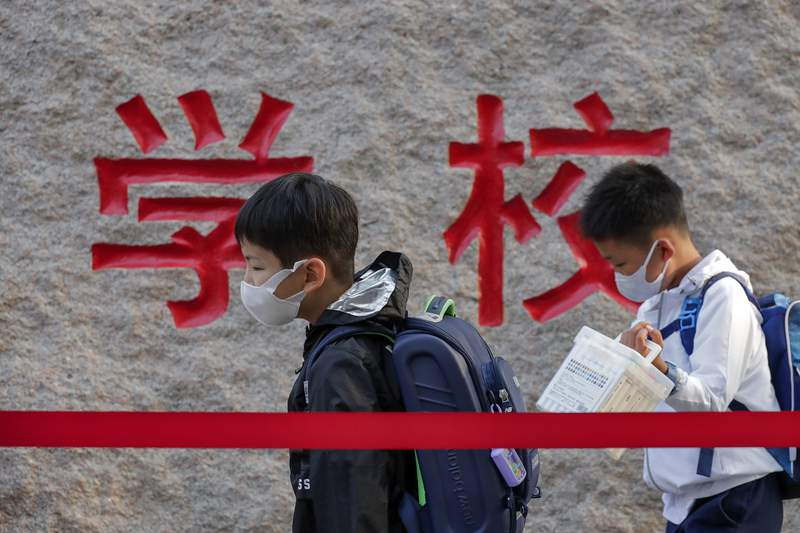 FILE - In this Sept. 7, 2020 file photo, students wearing face masks to help curb the spread of the coronavirus walk in line as they arrive at a primary school in Beijing.  Research suggests nearsightedness increased among Chinese schoolchildren during pandemic restrictions and online learning, and doctors think the same has happened in U.S. kids. A report on second- and third-graders published Thursday, Sept. 16, 2021,  in JAMA Ophthalmology is the latest to show the trend and the results echo those of two earlier Chinese studies. (AP Photo/Andy Wong, File)