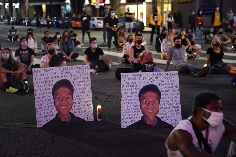 FILE - In this Aug. 24, 2020, file photo, two people hold posters showing images depicting Elijah McClain during a candlelight vigil for McClain outside the Laugh Factory in Los Angeles. An investigation into the arrest of McClain in suburban Denver criticizes how police handled the entire incident, faulting officers for their quick, aggressive treatment of the 23-year-old unarmed Black man and department overall for having a weak accountability system. (AP Photo/Jae C. Hong, File)