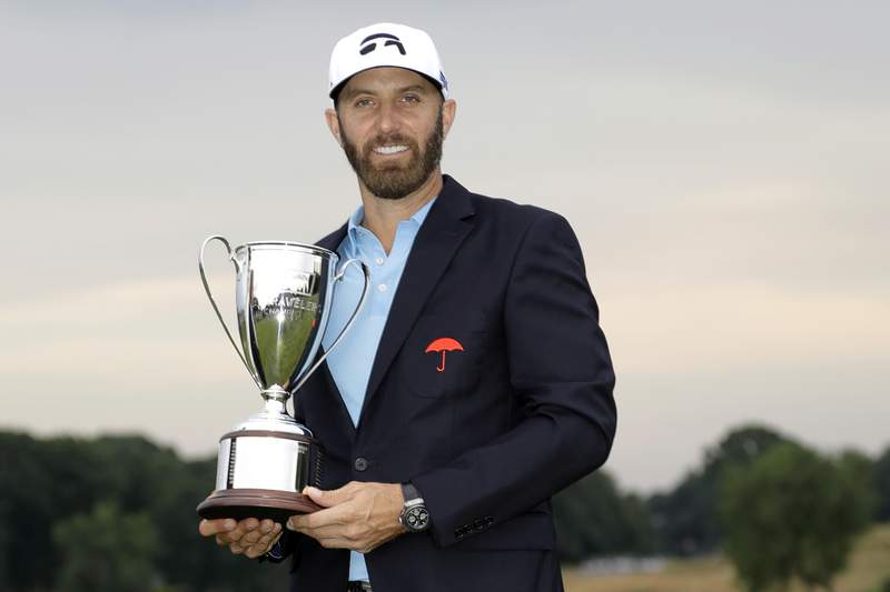 FILE  In this June 28, 2020, file photo, Dustin Johnson poses with the trophy after winning the Travelers Championship golf tournament at TPC River Highlands, Sunday, in Cromwell, Conn. Johnson says it was surreal sinking the final putt to win last year's Travelers Championship with fewer than 40 spectators politely clapping instead of the thousands that usually fill the bowl surrounding the 18th green at TPC River Highlands. (AP Photo/Frank Franklin II, File)