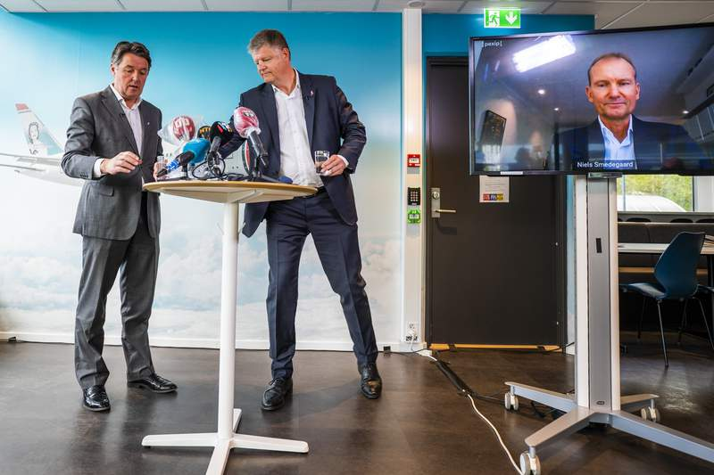 Three executives of Norwegian Air Shuttle company prepare for a media conference in Fornebu, Norway, with from left, CFO Geir Karlsen, CEO Jacob Schram and Chairman Niels Smedegaard on a video link, following their extraordinary general meeting Monday May 4, 2020.  The shareholders approved a crisis package which ensures further operation of the company impacted by the coronavirus. (Hakon Mosvold Larsen / NTB scanpix via AP)