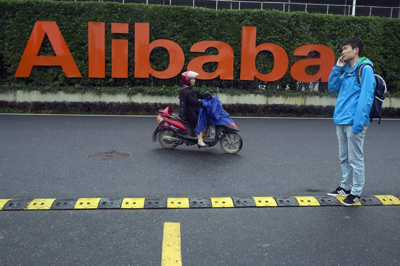 FILE - In this May 27, 2016, file photo, a man talks on his phone as a woman rides on an electric bike past a company logo at the Alibaba Group headquarters in Hangzhou in eastern China's Zhejiang province. Chinese authorities summoned 11 companies including Alibaba and Tencent for talks regarding the security of voice technology, as Beijing steps up scrutiny over the internet sector. (AP Photo/Ng Han Guan, File)