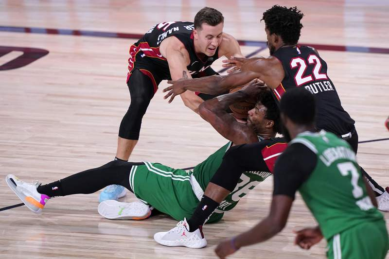 Boston Celtics' Jaylen Brown (7) looks on as Marcus Smart, center, struggles to maintain control of the ball against Miami Heat's Duncan Robinson, left, and Jimmy Butler (22) during the second half of an NBA conference final playoff basketball game, Saturday, Sept. 19, 2020, in Lake Buena Vista, Fla. (AP Photo/Mark J. Terrill)