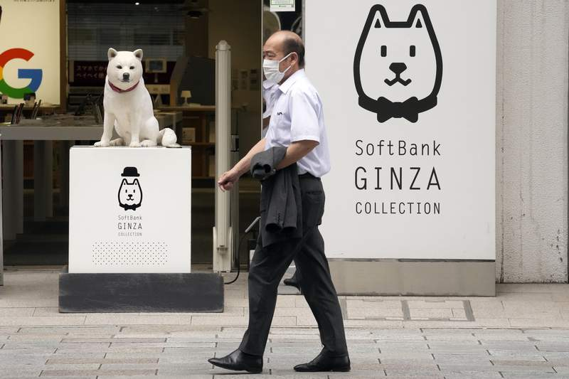 A man walks in front of a SoftBank shop in Tokyo on July 29, 2021. Japanese technology company SoftBanks fiscal first quarter earnings dropped 39% because of the absence of the cash from selling Sprint, which boosted profits a year ago. (AP Photo/Eugene Hoshiko)