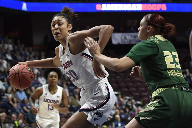 """FILE - Connecticut's Olivia Nelson-Ododa, left, drives around South Florida's Tamara Henshaw during the first half of an NCAA college basketball game in the American Athletic Conference tournament semifinals at Mohegan Sun Arena, Sunday, March 8, 2020, in Uncasville, Conn. UConn officials have discussed creating helmet stickers, warm-up T-shirts and altering athletic uniforms in other ways to show support for the Black Lives Matter movement. I believe as athletes that we have this platform, especially here, we have a platform and a voice and we should use it, especially on topics like this that have been going on for hundreds of years,"""" center Olivia Nelson-Ododa said last month. """"And so the ability to speak out about it and advocating for the Black Lives Matter movement is very important to me, and I know for the rest of my team as well. (AP Photo/Jessica Hill, File)"""
