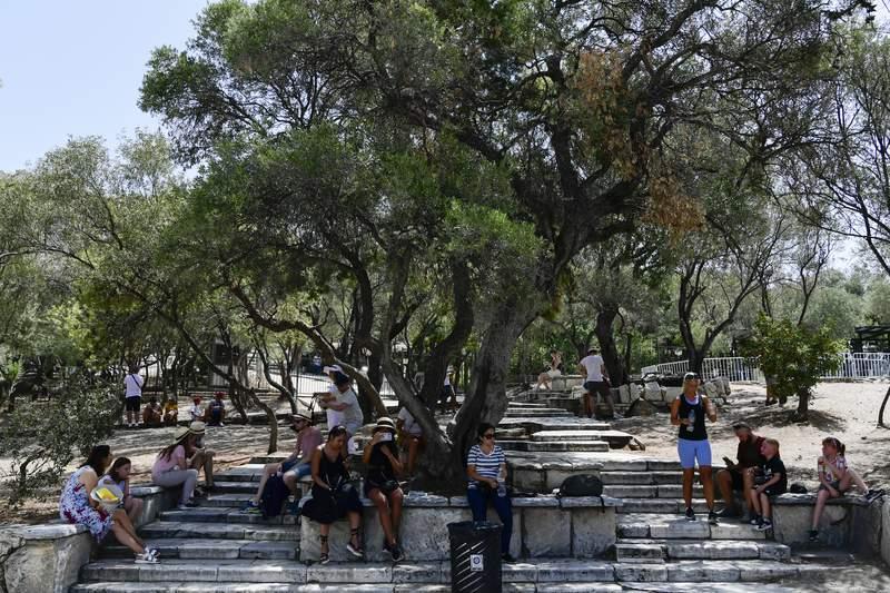 Turistas se resguardan del agobiante calor afuera de la antigua Acrpolis, en Atenas, Grecia, el 3 de agosto de 2021. Los termmetros en la capital griega han llegado a 42 grados. (AP Foto/Michael Varaklas)