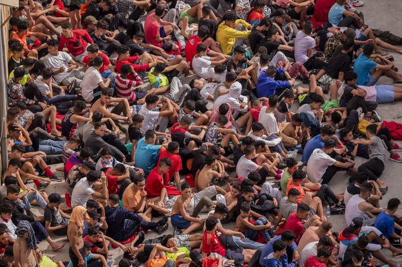 FILE - In this May 19, 2021 file photo, unaccompanied minors who crossed into Spain sit outside a warehouse used as temporary shelter as they wait to be tested for COVID-19 at the Spanish enclave of Ceuta, near the border of Morocco and Spain. Spain's interior minister Fernando Grande-Marlaska said Monday Aug. 16, 2021, that unaccompanied child migrants being sent back to Morocco wanted to go home, and denied accusations by rights groups of breaking international law and the return of the children from the Spanish enclave of Ceuta was not an expulsion. (AP Photo/Bernat Armangue, File)