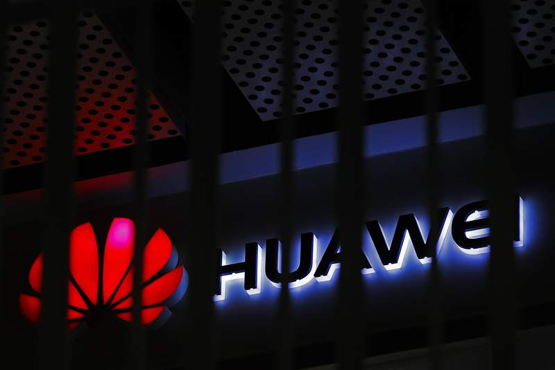 FILE - In this March 8, 2019, file photo, A logo of Huawei retail shop is seen through a handrail inside a commercial office building in Beijing.  The U.S. government is imposing new restrictions on Chinese tech giant Huawei by limiting its ability to use American technology to build its semiconductors. The Commerce Department said Friday, May 15, 2020 the move aims to cut off Huaweis undermining of existing U.S. sanctions.  (AP Photo/Andy Wong, File)