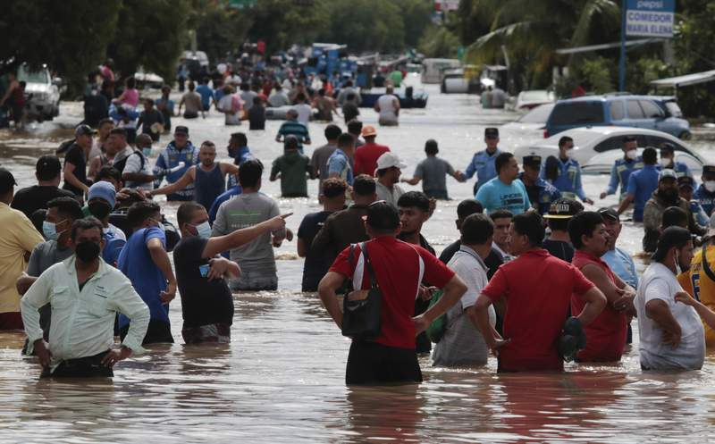 Mltiples personas vadean un camino inundado el jueves 5 de noviembre de 2020 tras el paso del huracn Eta, en Planeta, Honduras. (AP Foto/Delmer Martnez)