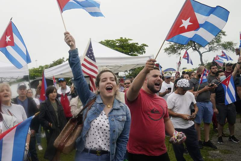 Demonstrators wave Cuban flags during a rally, Tuesday, July 13, 2021, in Miami. (AP Photo/Marta Lavandier)