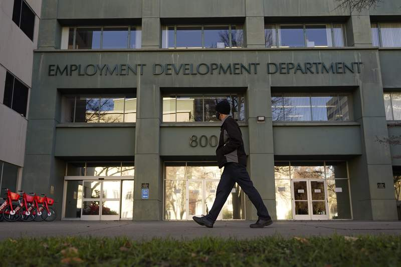 FILE - In this Dec. 18, 2020, file photo, a person passes the office of the California Employment Development Department in Sacramento, Calif.  Americans who lost their job or some of their income in 2020 should pay attention to a new, one-time provision that ensures they dont lose access to valuable tax credits as well.   (AP Photo/Rich Pedroncelli, File)
