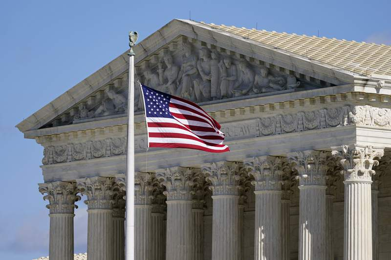 FILE - In this Nov. 2, 2020, file photo an American flag waves in front of the Supreme Court building on Capitol Hill in Washington. The Supreme Court is hearing arguments over whether the Trump administration can exclude people in the country illegally from the count used for divvying up congressional seats. (AP Photo/Patrick Semansky, File)