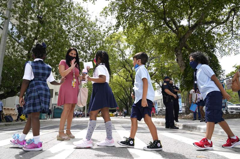 FILE - In this Monday, Aug. 23, 2021, file photo, teacher Vanessa Rosario greets students outside of iPrep Academy on the first day of school, in Miami. Florida school districts can legally require their students to wear masks to prevent the spread of COVID-19, a judge ruled Friday, Aug. 27, saying Gov. Ron DeSantis overstepped his authority when he issued an executive order banning such mandates. (AP Photo/Lynne Sladky, File)