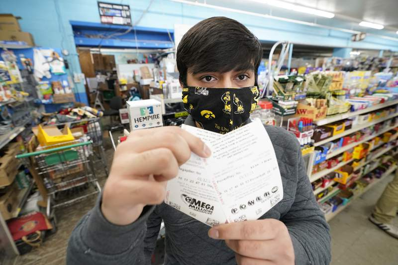 Hardik Kalra, of Des Moines, Iowa, poses for a photo with his Mega Millions and Powerball lottery tickets.