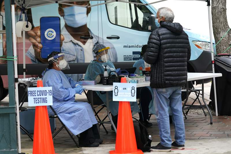 Health care workers offer free COVID-19 testing from a Miami-Dade County mobile van outside of an early voting site, Monday, Oct. 19, 2020, in Miami. Florida begins in-person early voting for the general election in much of the state Monday. (AP Photo/Lynne Sladky)