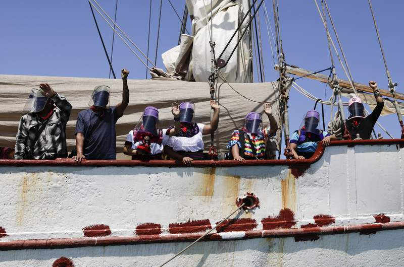 ARCHIVO - En esta foto del 30 de abril del 2021, una delegacin del Ejrcito Zapatista de Liberacin Nacional saluda desde el barco que les llevar a Europa en ocasin del 500mo aniversario de la conquista de Mxico, desde Isla de Mujeres, en el estado de Quintana Roo. La delegacin se quej el martes, 15 de junio del 2021, que el gobierno mexicano dificult para sus miembros la obtencin de pasaportes para el viaje a Espaa. (AP Foto/Eduardo Verdugo)
