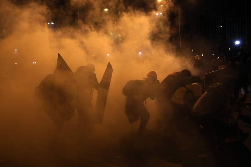Manifestantes buscan resguardo del gas lacrimgeno lanzado por la polica para dispersar a los manifestantes reunidos en la Plaza San Martn en repudio del nuevo gobierno del presidente Manuel Merino, en Lima, el sbado 14 de noviembre de 2020. (AP Foto/Rodrigo Abd)
