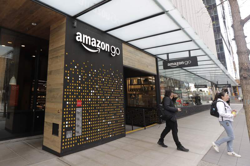 FILE - In this March 4, 2020 file photo, people walk out of an Amazon Go store, in Seattle. Amazon is rolling out a new device for contactless transactions that will scan an individuals palm. The Amazon One, which will initially launch in two Amazon Go stores in Seattle, is being viewed as a way for people to use their palm to make everyday activities like paying at a store easier. (AP Photo/Ted S. Warren, File)
