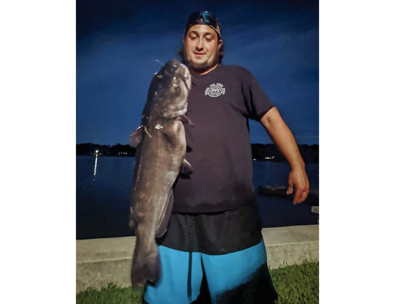 FILE - This Aug. 21, 2021, file photo provided by Chris Braga, shows Ben Tomkunas holding a catfish he caught in Coventry, Conn., that was thought to have smashed a state record weighing 21.3-pounds. But uncertainty about the species of the catfish caught that was eaten before it could be vetted by authorities in August has led a Connecticut agency to withdraw its awarding of a new state record for largest white catfish. (Chris Braga via AP, File)