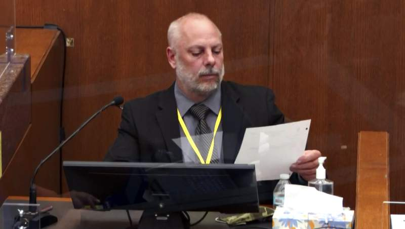 In this image from video, witness David Pleoger, a retired Minneapolis police sergeant reviews a document during testimony as Hennepin County Judge PeterCahill presides Thursday, April 1, 2021, in the trial of former Minneapolis police Officer Derek Chauvin at the Hennepin County Courthouse in Minneapolis, Minn. Chauvin is charged in the May 25, 2020 death of George Floyd. (Court TV via AP, Pool)