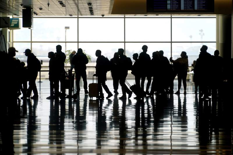 FILE - In this Wednesday, March 17, 2021 file photo, travelers walk through the Salt Lake City International Airport in Salt Lake City. Mother's Day weekend meant bigger crowds at U.S. airports. The Transportation Security Administration said its agents screened slightly more than 1.7 million people on Sunday, May 9 the highest number since March 2020, when travel was collapsing because of the coronavirus pandemic.  (AP Photo/Rick Bowmer, File)
