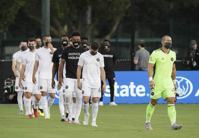 Inter Miami players enter the field for an MLS soccer match against Orlando City, Wednesday, July 8, 2020, in Kissimmee, Fla., some wearing shirts and masks with messages about race. (AP Photo/John Raoux)