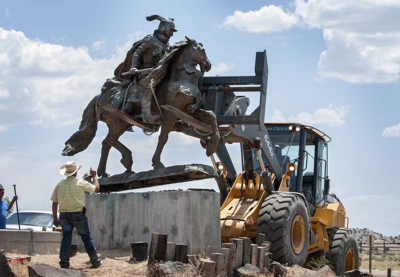 Rio Arriba County workers remove the bronze statue of Spanish conquerer Juan de Oate from its pedestal in front of a cultural center in Alcalde, N.M., Monday, June 15, 2020. Crowds of people for and against the removal lined Highway 68 near of the center. (Eddie Moore/The Albuquerque Journal via AP)