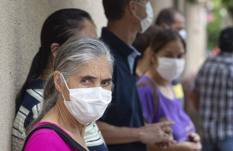 Seventy-year-old Marlene Negrao waits in line outside a public school to get a shot of China's Sinovac CoronaVac vaccine in Serrana, Sao Paulo state, Brazil, Wednesday, Feb. 17, 2021. Brazil's Butantan Institute has started a mass vaccination on Wednesday of the city's entire adult population, about 30,000 people, to test the virus' behaviour in response to the vaccine. (AP Photo/Andre Penner)