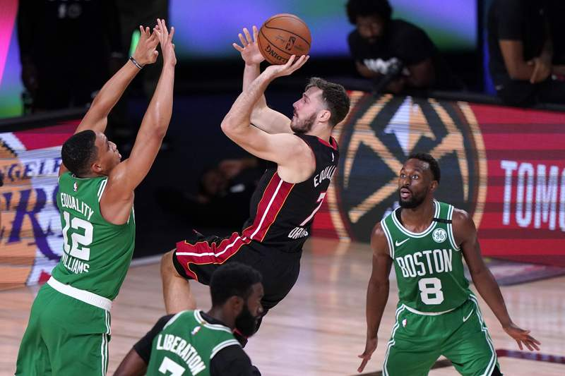 Miami Heat guard Goran Dragic (7) goes up for a shot between Boston Celtics' Grant Williams (12), Jaylen Brown, bottom, and Kemba Walker (8) during the second half of an NBA conference final playoff basketball game, Saturday, Sept. 19, 2020, in Lake Buena Vista, Fla. (AP Photo/Mark J. Terrill)