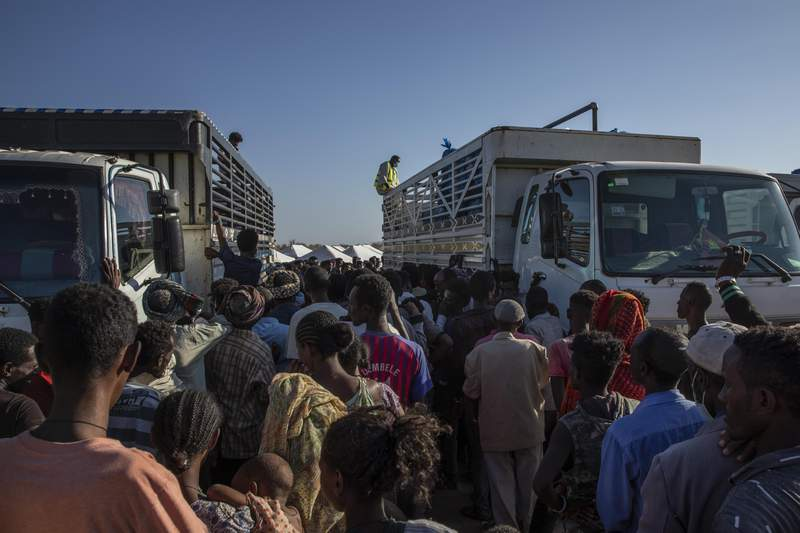 FILE - In this Tuesday, Nov. 24, 2020 file photo, Tigray refugees who fled the conflict in Ethiopia's Tigray region, wait to receive aid at Umm Rakouba refugee camp in Qadarif, eastern Sudan. Many of the hospitals outside the capital of Ethiopias conflict-hit Tigray region were struck by artillery during two months of recent fighting. That's according to the first humanitarian assessment of the devastation as aid is beginning to arrive with desperately needed supplies. The scale of the damage has been largely unknown while Ethiopian forces pursue and clash with those of the now-fugitive Tigray regional leaders. Transportation and communications links were severed. People who fled the region have told The Associated Press and others of looting and the burning of homes. The new assessment does not say who fired at hospitals. (AP Photo/Nariman El-Mofty, File)