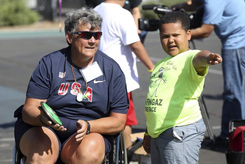 FILE - In this May 2, 2015, file photo, Paralympian Angela Madsen, left, works with Los Angeles Unified School District students during Ready, Set, Gold! Day at Trinity Street Elementary in Los Angeles. A three-person crew left the Hawaii Yacht Club Wednesday, July 29, 2020, to search for the craft piloted by Angela Madsen, who died in the Pacific Ocean last month, The Honolulu Star-Advertiser reported Thursday. (Photo by Matt Sayles/Invision for Samsung/AP Images, File)