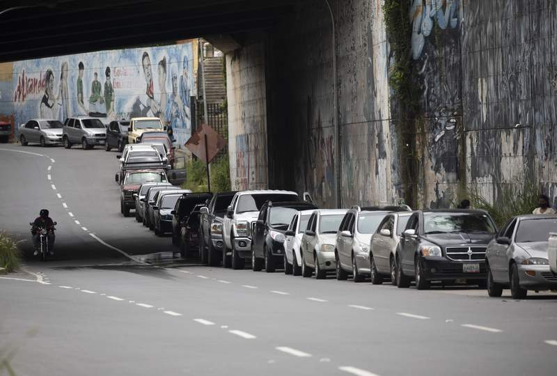 FILE - In this Sept 8, 2020 file photo, vehicles line up near a gas station to fill their tanks in Caracas, Venezuela. Maritime safety mechanisms have become a powerful mechanism for tracking ships engaged in rogue activities like transporting sanctioned crude oil to and from places under U.S. or international sanctions like Venezuela. (AP Photo/Ariana Cubillos, File)