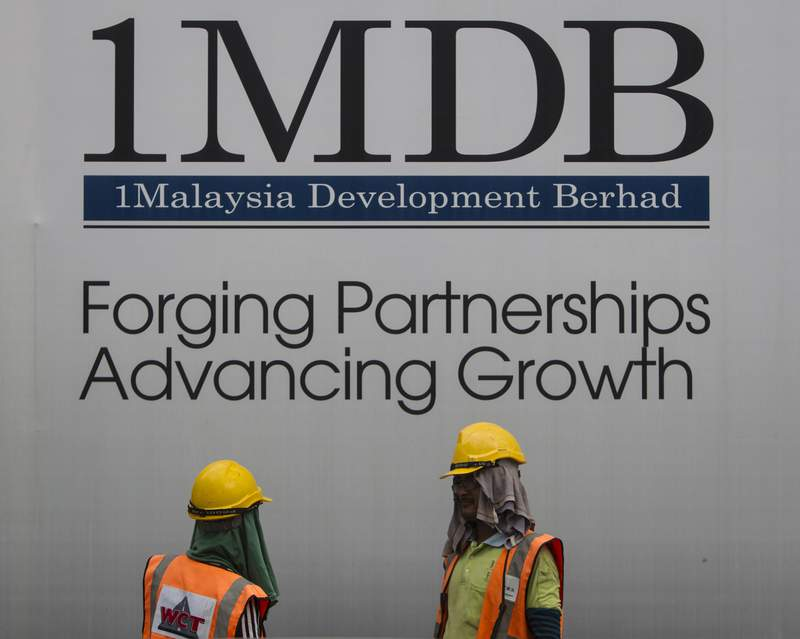 FILE - In this May 14, 2015, file photo, construction workers chat in front of a billboard for state investment fund 1 Malaysia Development Berhad (1MDB) at the fund's flagship Tun Razak Exchange development in Kuala Lumpur, Malaysia. Malaysia's Finance Ministry said Monday, May 10, 2021 that sovereign wealth fund 1MDB and a former subsidiary have filed 22 lawsuits to recover assets worth over $23 billion from various institutions and individuals. (AP Photo/Joshua Paul, File)